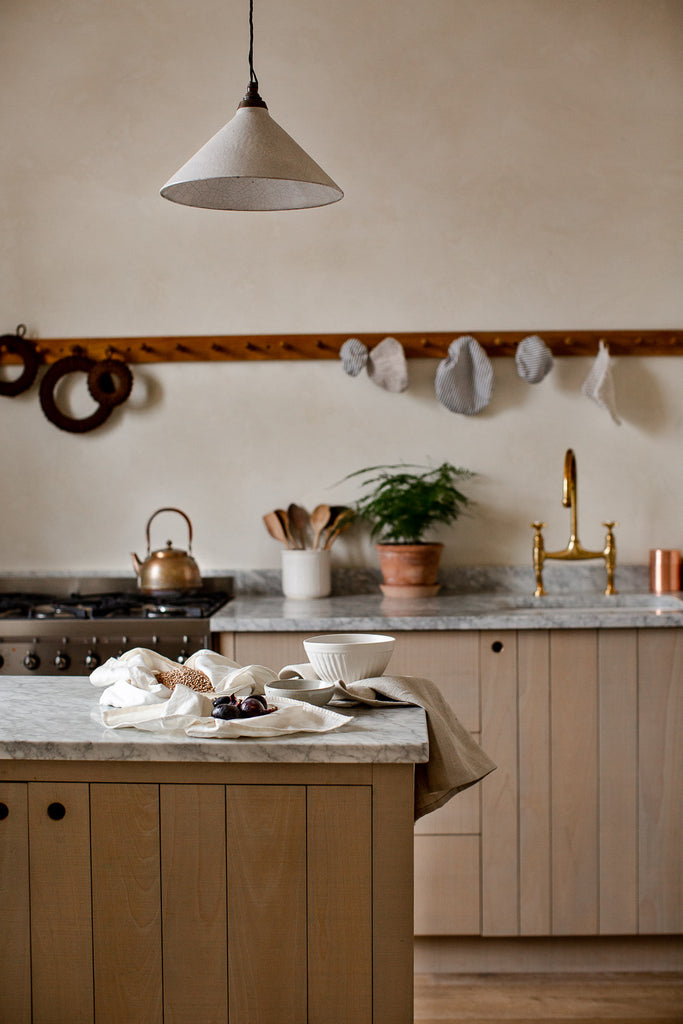 wooden kitchen with marble and cream venetian plaster walls