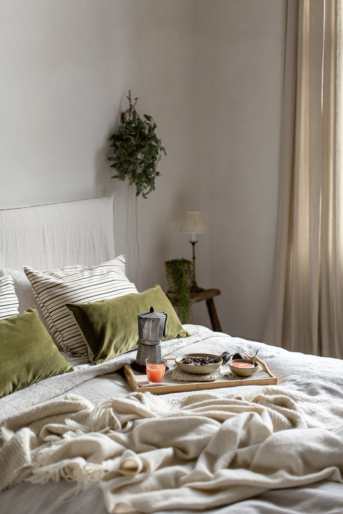 natural bedroom with linen in neutral colours and green