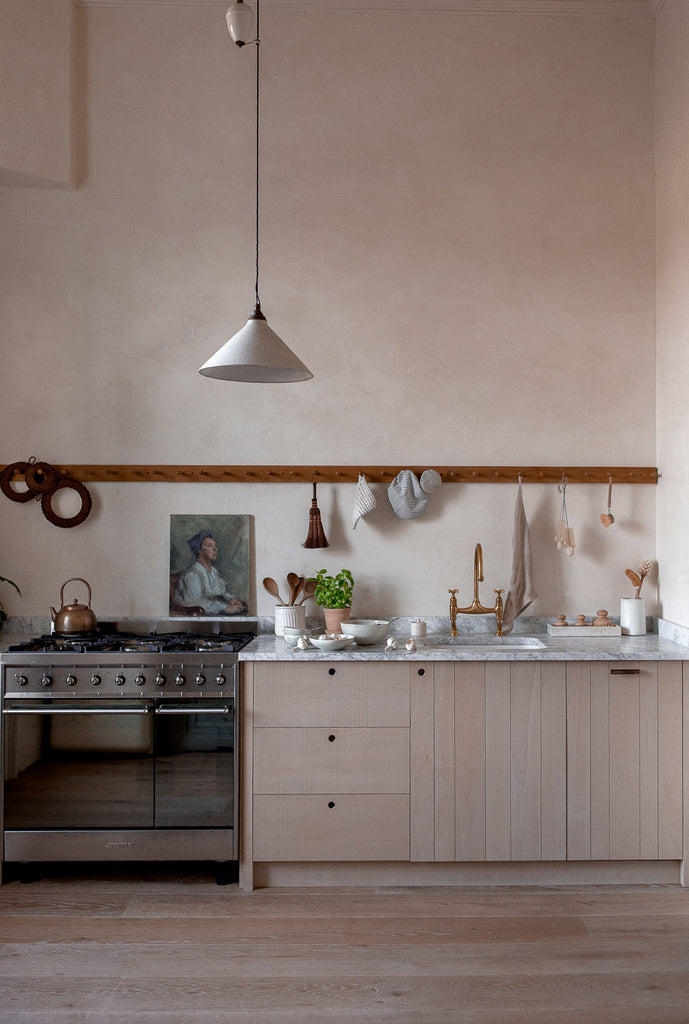 natural kitchen in neutral colours with oil painting portrait