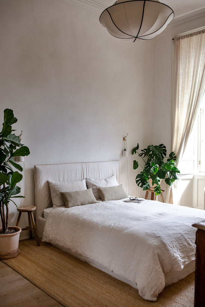 natural bedroom decor with linen bedding, plants and jute rug