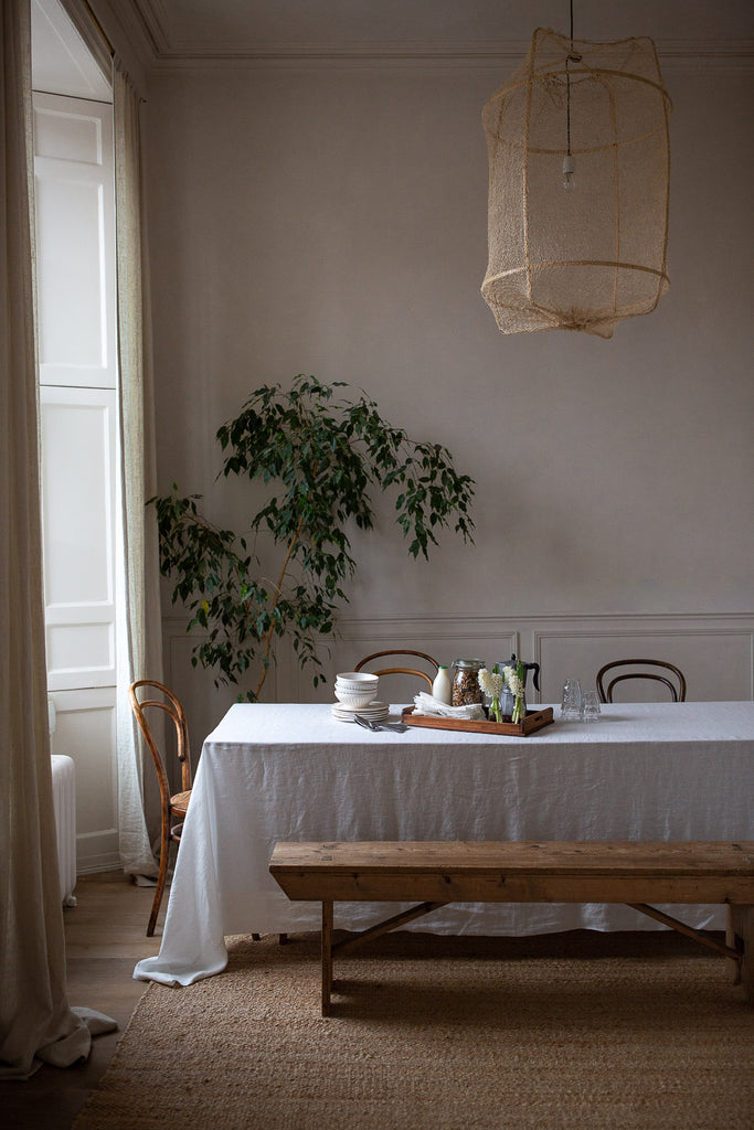 Natural dining room table with linen tablecloth