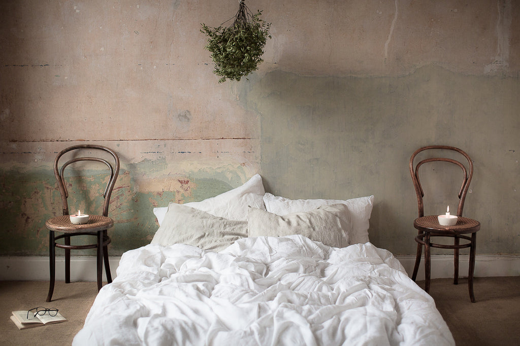 Bare stripped walls and linen bedding