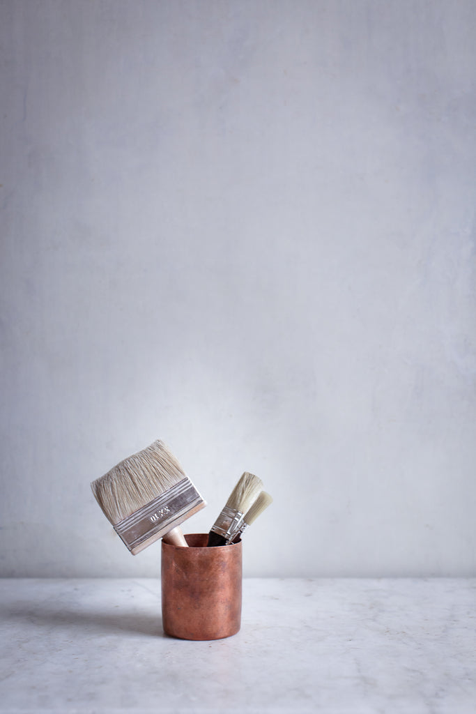 copper cup with paintbrushes