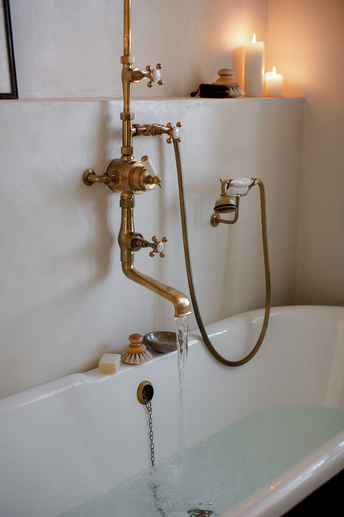 natural bathroom with claw foot bathtub and brass taps