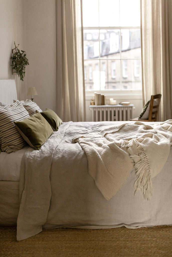 natural bedroom with jute rug, linen bedding and green