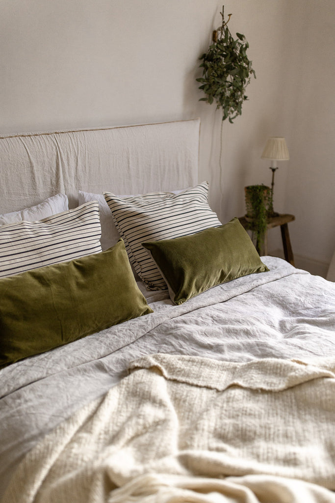 natural bedroom decor in neutral colours with green velvet, linen and wool
