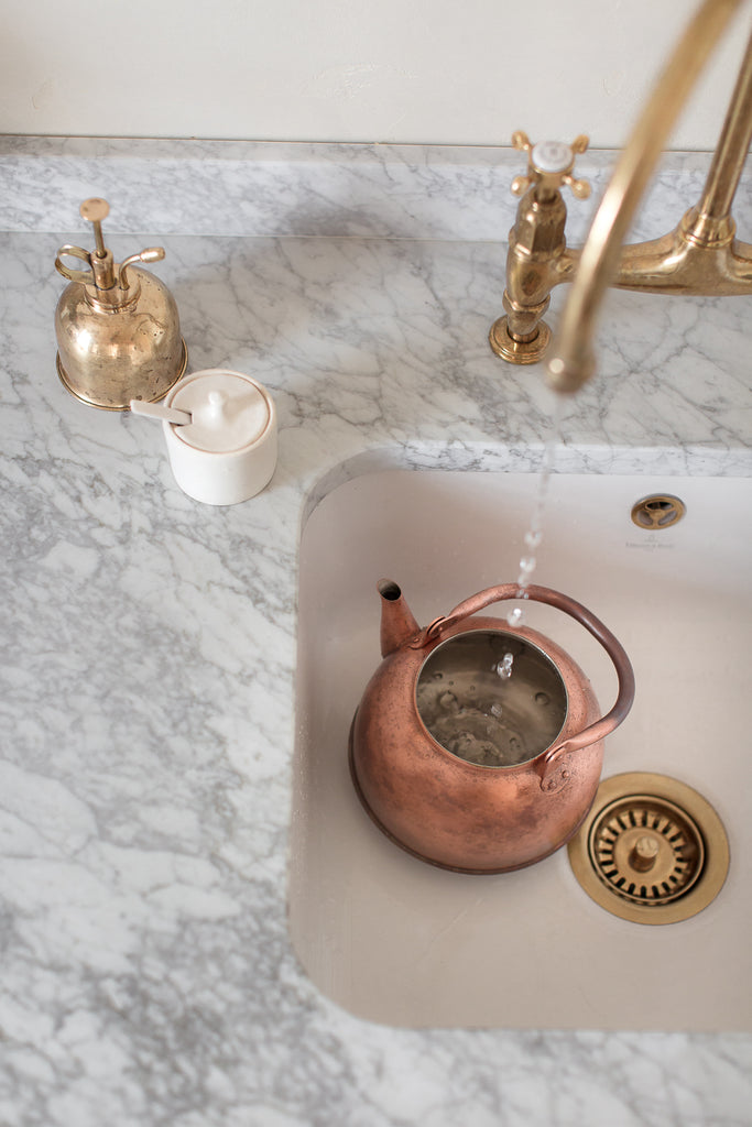 copper kettle with patina on marble worktop