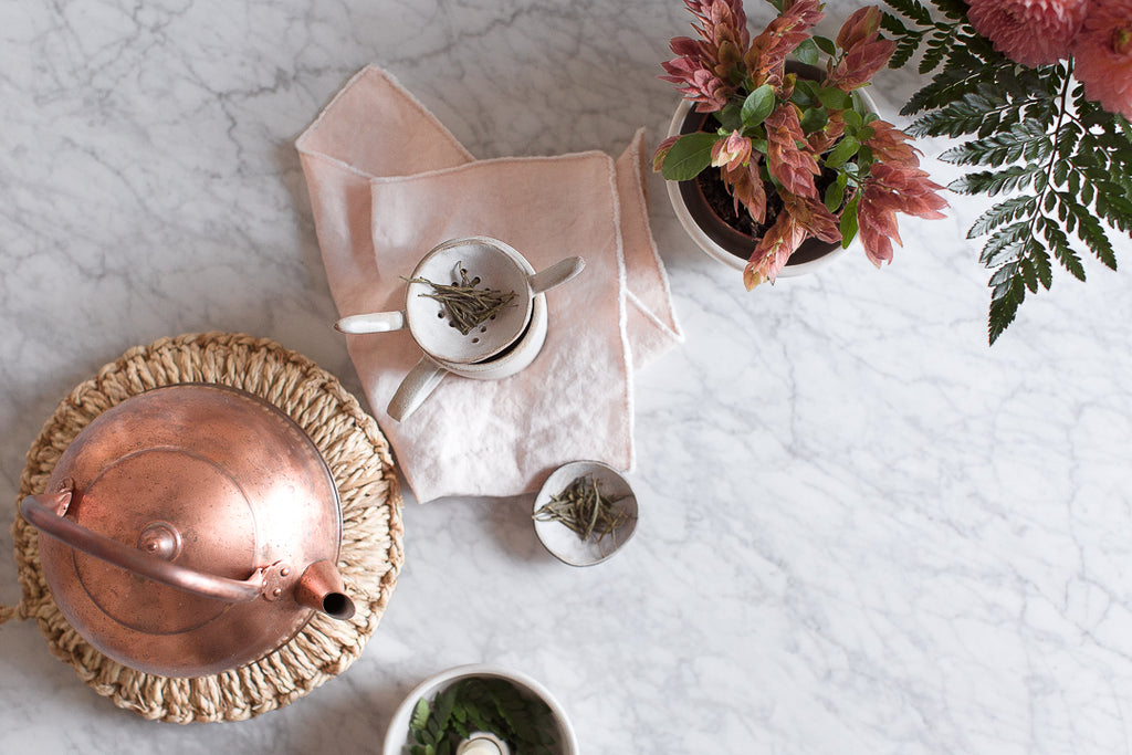copper kettle, marble worktop pink linen napkin, handmade ceramic mug in grey