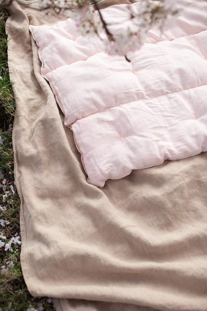 linen blanket and pink mattress cushion