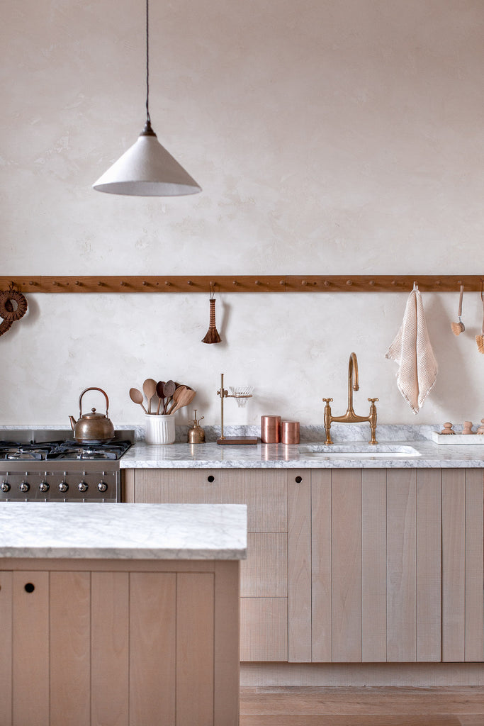 natural wood kitchen with marble and plaster walls