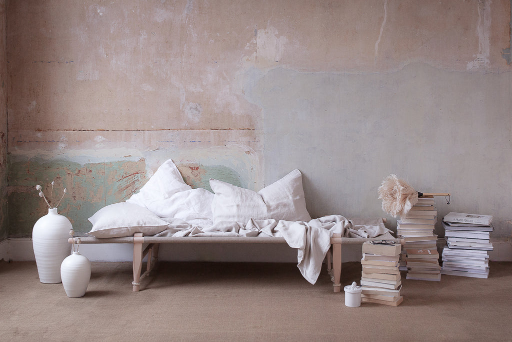 INGREDIENTS LDN Bedroom decor with plaster walls, book stacks and daybed