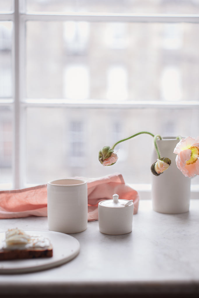 Matte glazed ceramics and pink linen on marble
