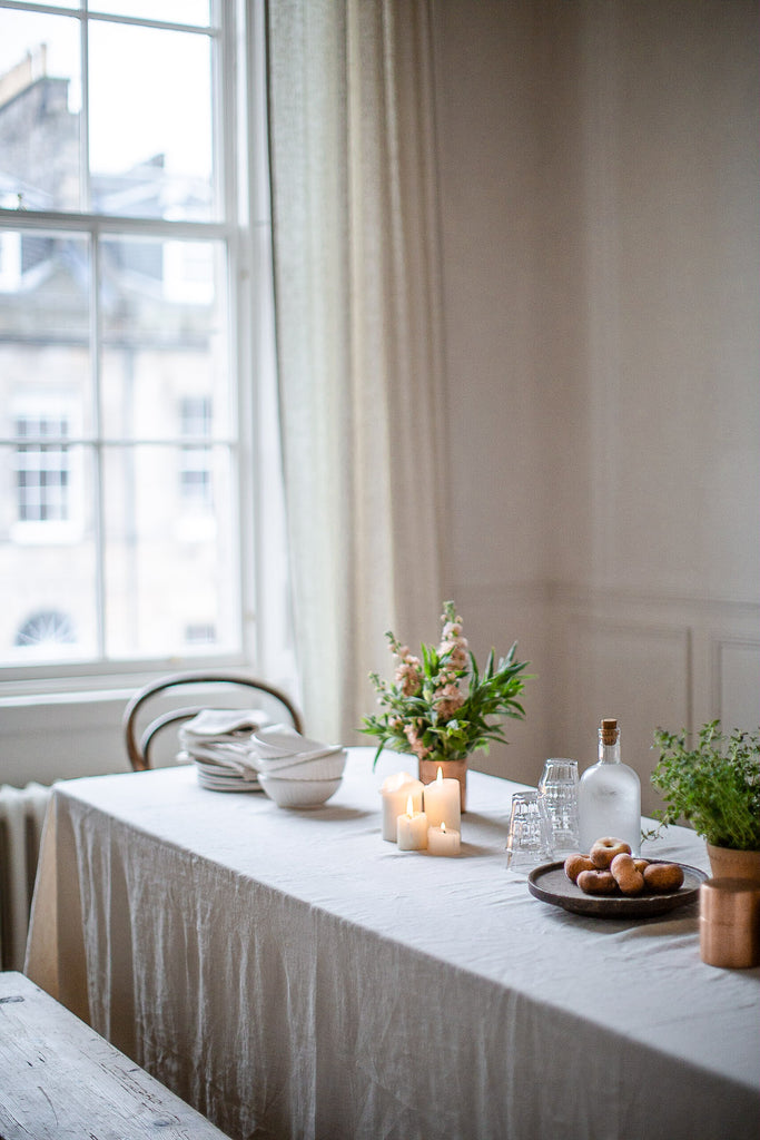 warm natural table setting with cream linen tablecloth