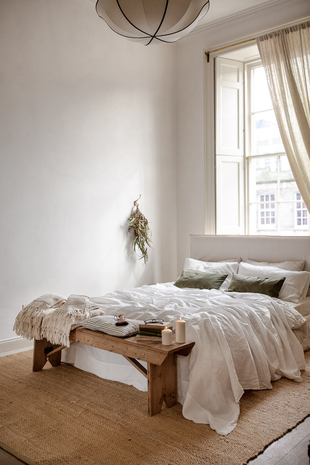 neutral bedroom with linen bedding and jute rug