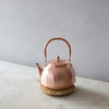 Japanese copper kettle on straw trivet