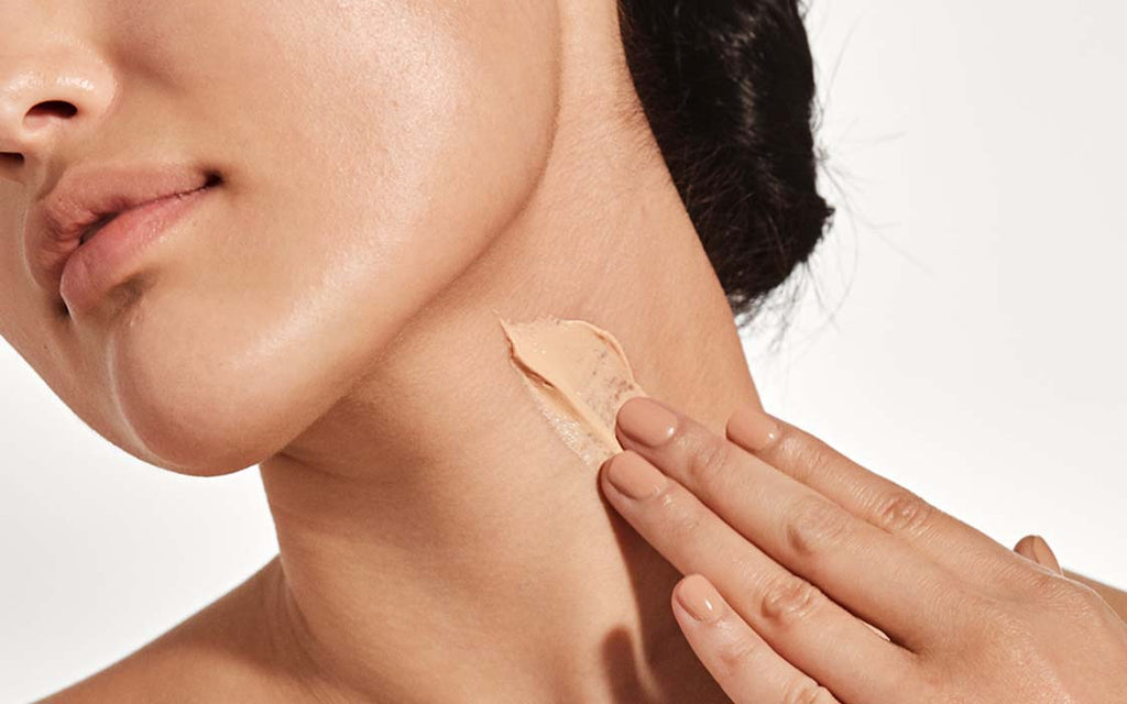 Applying skincare product on neck