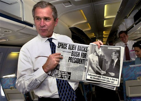 George W. Bush holds an issue of the Weekly World News that claims that a space alien endorses Bush for President.
