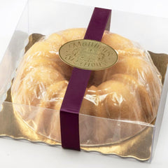 Lemon Rum Bundt cake in clear gift box with plum ribbon