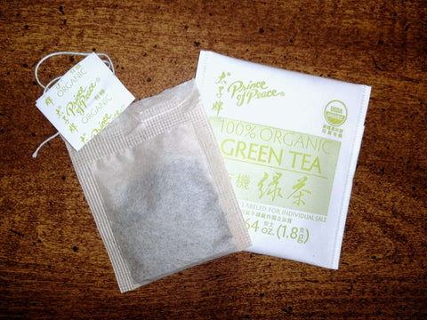 Opened packet and a teabag of Prince of Peace organic green tea