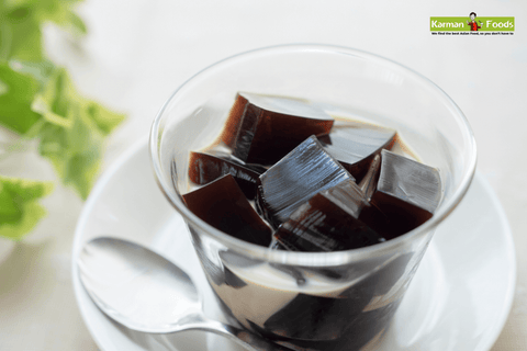 A clear glass filled brim with coffee almond jelly milk tea on a white saucer