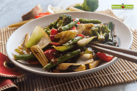 A dish of stir-fried vegetables in a savory sauce with chopsticks on the side