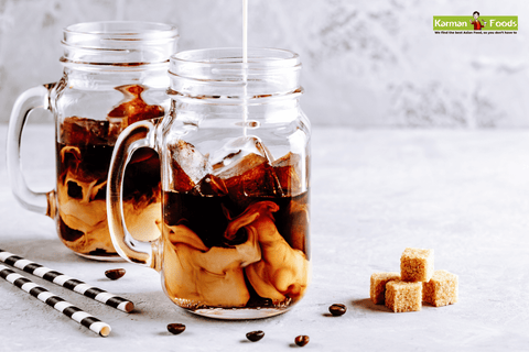 2 mason jars with ice, coffee, and milk surrounded with sugar cubes, wafer sticks, and coffee beans.