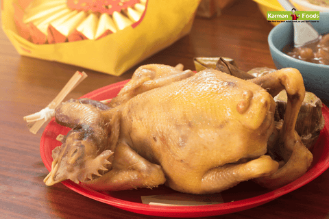 A whole simmered chicken on a big red plate on a table
