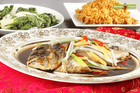 A whole steamed fish with ginger, garlic & soy sauce on a big plate on top of a table covered with red cloth