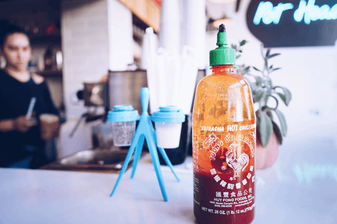 A half-filled bottle of Huy Fong Sriracha hot chili sauce on a table