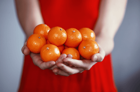 A girl on a red dress holding tangerines