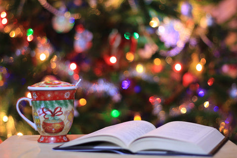 an open book beside a Christmas mug and Christmas tree in the background