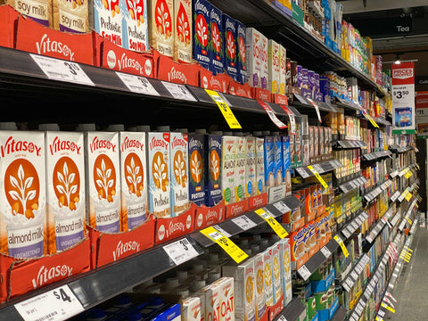 A wide selection of Vitasoy Soy Milk products stacked neatly in a grocery store.
