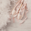 Pink ballet slippers next to fluffy white rug