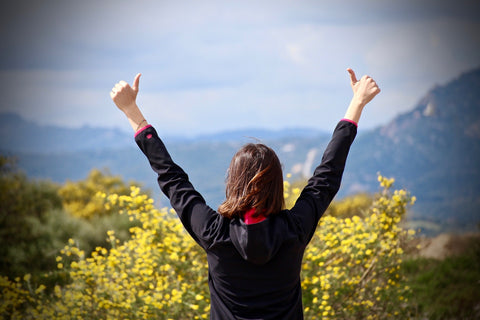 Woman on hilltop with arms extended with both thumbs up