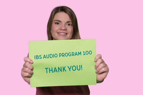 Smiling woman holding a sign reading Thank you IBS Audio Program 100