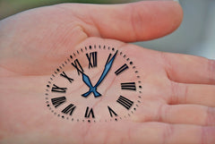 clock ink stamped on open palm of left hand of an adult