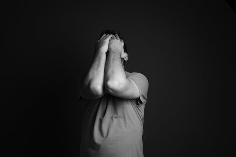 Man with hands held up to his face in despair