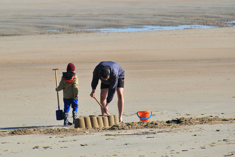 Photo of man and child on beach having fun digging in the sand
