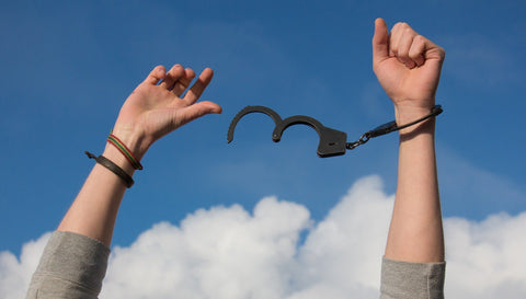 Hands held up to the blue sky, with handcuff hanging off one wrist, white clouds are seen in the distance