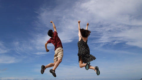 Photo of man and woman jumping for joy on hillside with blue sky and white clouds in the background