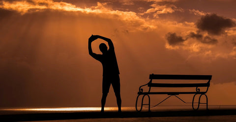 Man doing stretching exercises by a red dawn coastal dawn