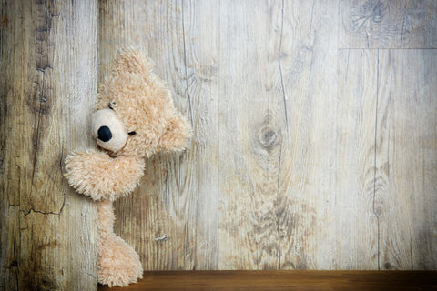 Picture of a teddy bear peek out behind a door