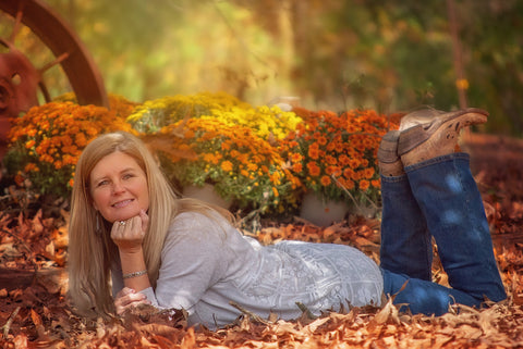 Lady looking happy lying in autumn leaves