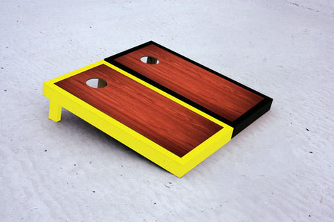Custom cornhole boards with black and yellow borders with Rosewood stained center