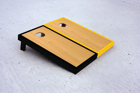 Custom cornhole boards with black and yellow borders with natural stained center
