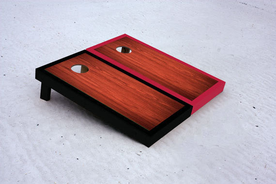 Custom cornhole boards with black and red borders with rosewood stained center