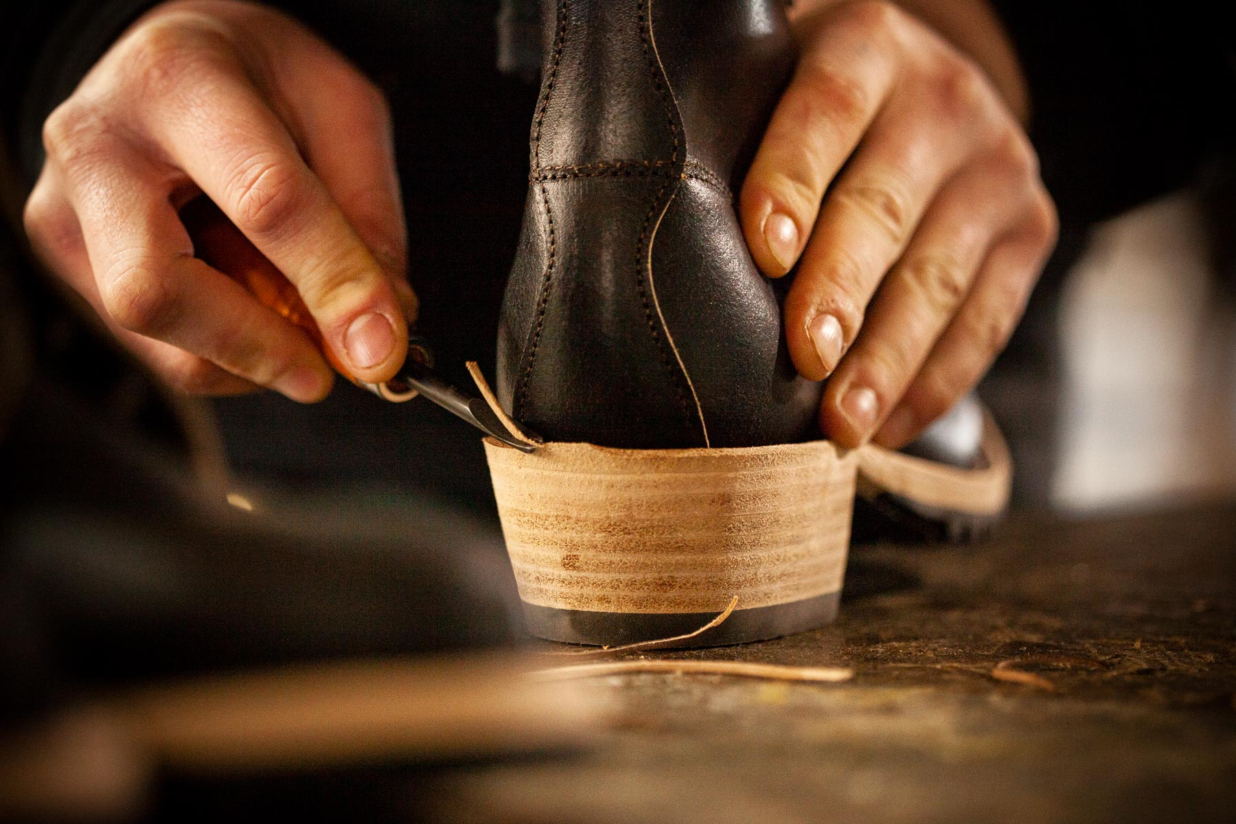 Close-up shot of hands finishing the leather edge of the heel of a women's boot