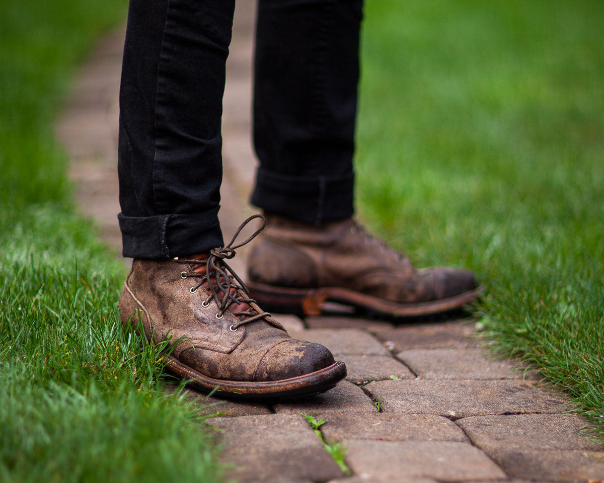 Man in leather boots standing on brick path