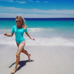 Swimwear modelling wearing aqua swimsuit running from wave at the beach