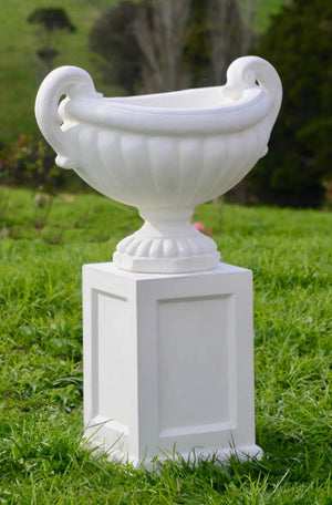 The Faraway Garden Amalfi Urn is an elegant garden planter inspired by the classical aesthetic of Ancient Greece with its distinctive swan shaped handles and linear moulding around bowl. Pictured here on our Tarrant Pedestal.  This unique garden planter would look gorgeous as part of a group or positioned on a Faraway Garden pedestal and the focal point at the end of pathway or the centrepiece of a rose garden.